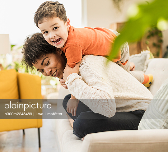 Cheerful mother and son playing while sitting on sofa at home - p300m2243489 by Uwe Umstätter