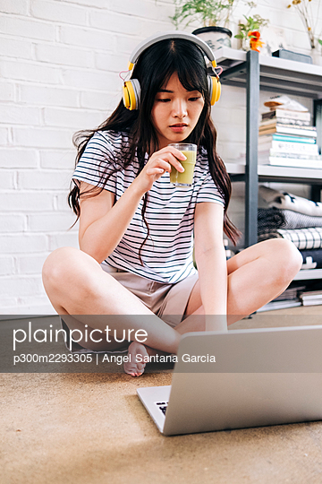 Woman with headphones using laptop while drinking smoothie at home - p300m2293305 by Angel Santana Garcia