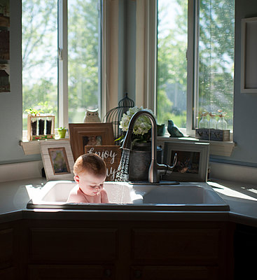 Shirtless baby boy sitting in kitchen sink against windows at home - p1166m1512402 by Cavan Images
