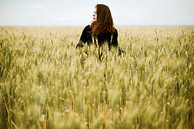 Young woman stands in a wheat field in summer - p1166m2106149 by Cavan Images