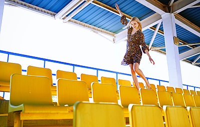 Young adult blond woman having fun at the empty stadium with yellow seats - p1577m2260492 by zhenikeyev