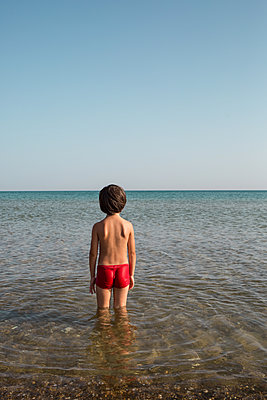 Little boy standing by the sea - p1623m2290998 by Donatella Loi
