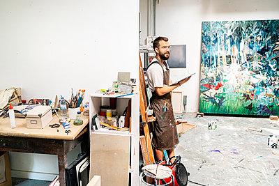 Artist standing in his studio, holdong digital tablet - p300m2156595 by Peter Scholl