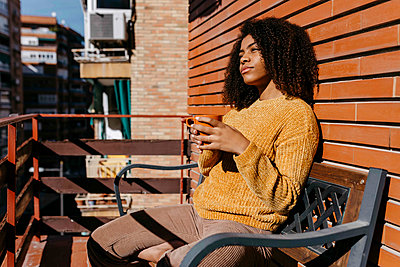 Thoughtful woman with coffee cup looking away while sitting at balcony - p300m2256658 by Tania Cervián