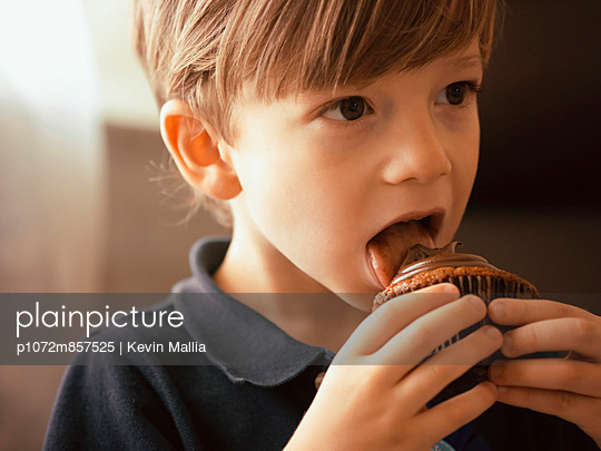 4 year Old Boy licking chocolate frosting from a cupcake - p1072m857525 by Kevin Mallia