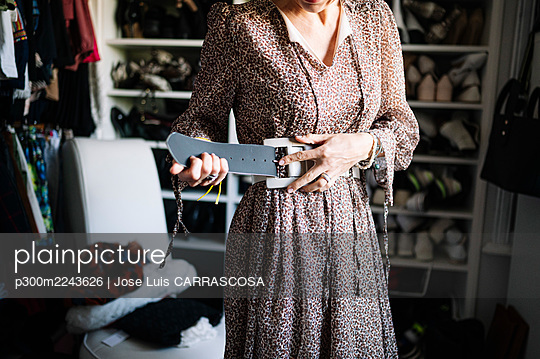 Mid adult woman fastening new belt in wardrobe at home - p300m2243626 by Jose Luis CARRASCOSA