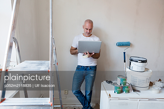 Mid adult man looking at laptop during apartment renovation - p352m2118835 by Ulf Isacson
