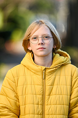 Tween boy with glasses and yellow jacket smiling looking at camera - p1166m2171635 by Cavan Images