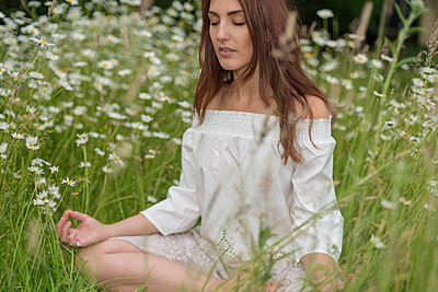 Young woman meditating in a field of marguerites - p1433m1585141 by Wolf Kettler