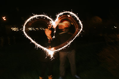 Sparklers shaping a heart at night - p1507m2196571 by Emma Grann