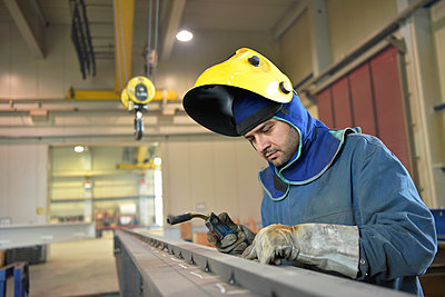 Welder checking metal surface in factory - p300m1581023 by lyzs