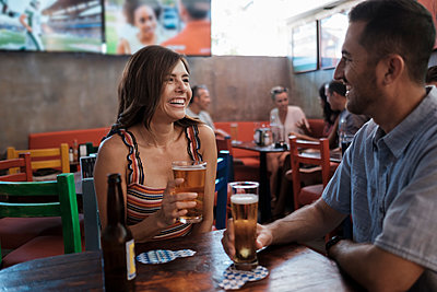 Happy couple drinking beer in a bar - p300m2078567 by André Babiak