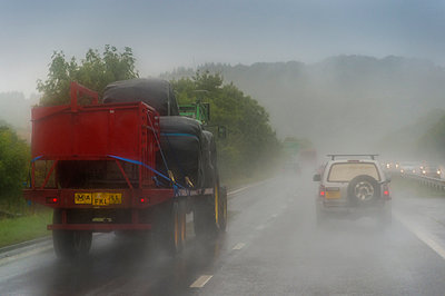 Tractor with trailer on highway in rain - p300m973745 by Frank Röder