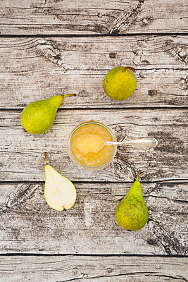 Whole and sliced organic pears and glass of pear jam on grey wood - p300m977804f by Larissa Veronesi