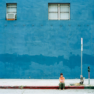 Woman sitting in front of blue building - p312m1054612f by Stefan Isaksson