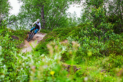 Mountain biker tackles a corner in Valadalen, Sweden. - p343m1090337 by Elias Kunosson