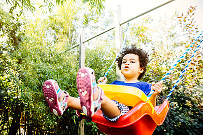 Low angle view of mixed race girl playing on swing - p555m1421588 by Inti St Clair photography