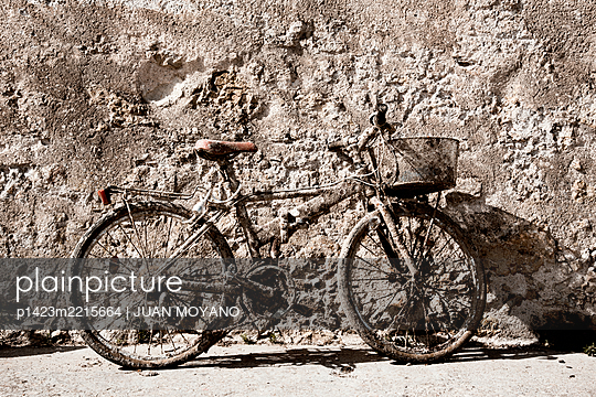 Rusty bicycle leaning on a rustic wall - p1423m2215664 by JUAN MOYANO