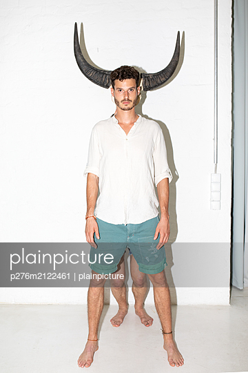 Young horned man - p276m2122461 by plainpicture