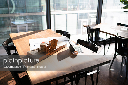 Architectural model and blueprint with laptop on table at office cafeteria - p300m2287611 by Florian Küttler