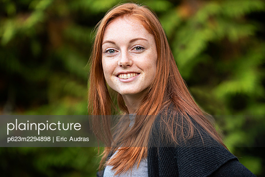 Portrait of smiling young woman in park - p623m2294898 by Eric Audras