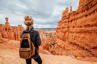 Rear view of woman standing against rock formations at Bryce Canyon National Park - p1166m1229413 by Cavan Images