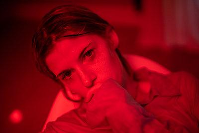 Junge Frau in rotem Licht - p1321m2141708 von Gordon Spooner