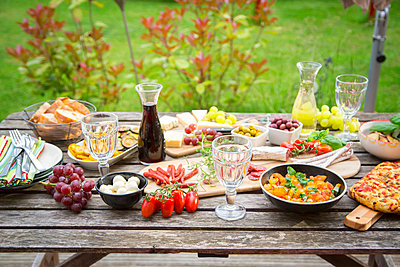 Variety of Mediterranean antipasti on garden table - p300m1153505 by Sandra Roesch