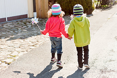 Two girls walking and holding hands - p312m1113854f by Rebecca Wallin