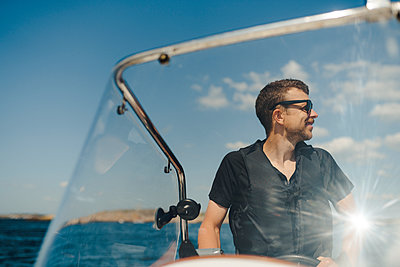 Man steering boat - p312m2146226 by Stina Gränfors
