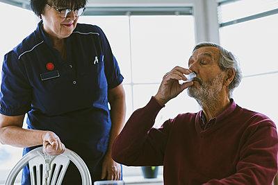 Caretaker looking at senior man taking medicine - p426m1468229 by Maskot