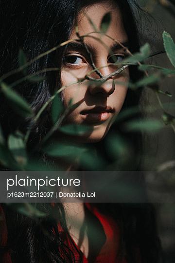 Mädchen hinter einem Busch - p1623m2212037 von Donatella Loi
