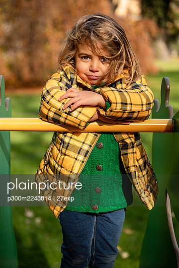 Girl standing with arms crossed on play equipment at park - p300m2243814 by 27exp