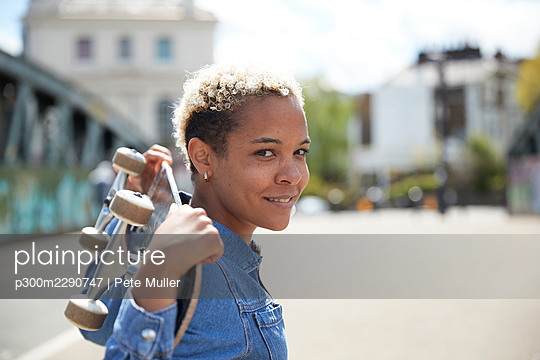 Smiling woman carrying skateboard on shoulder during sunny day - p300m2290747 by Pete Muller