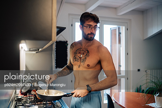 Mid adult man with tattoos cooking breakfast in frying pan - p924m2097433 by Eugenio Marongiu