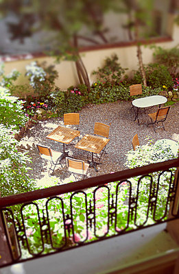 View from Paris hotel room overlooking tables in courtyard garden - p1072m829466 by Neville Mountford-Hoare