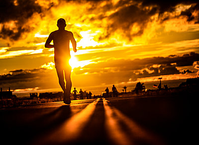 Runner at sunset, triathlon, Ironman, Hawaii - p1211m2168125 by Danny Weiss