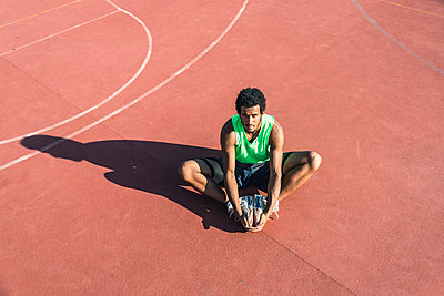 Young basketball player stretching leg - p300m1581055 by Francesco Morandini