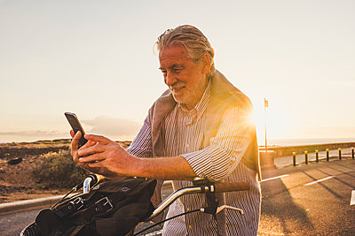 Senior man using smartphone on bicycle at sunset, Tenerife - p300m2155763 von Simona Pilolla