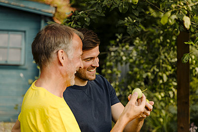 Smiling father and son looking at granny smith apple in front of tree - p300m2275028 by Gustafsson