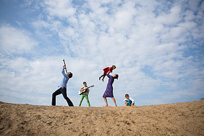 Low angle view of family enjoying on sand dune against cloudy sky - p301m1101895f by Sven Hagolani