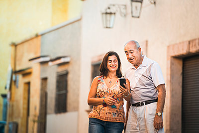 Hispanic father and daughter using cell phone in city - p555m1420474 by Sollina Images