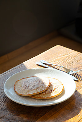 Two Pancakes with Powdered Sugar on Plate - p694m2218921 by Novo Images