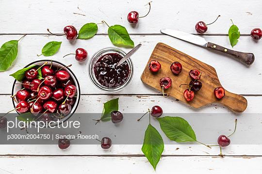 Jar of cherry jam and cherries on white wood - p300m2004750 von Sandra Roesch