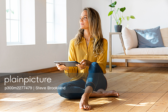Woman with digital tablet looking away while sitting on floor in living room - p300m2277479 by Steve Brookland