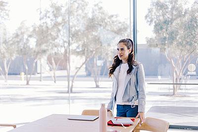 Beautiful woman looking away by coffe shop - p1166m2095862 by Cavan Images