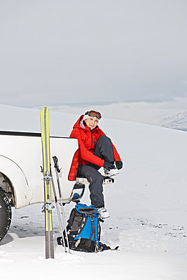 woman sitting on the back of pick up truck taking a break from skiing - p1166m2268497 by Cavan Images