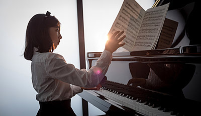 Adorable schoolgirl playing piano in music school - p1315m2003041 by Wavebreak