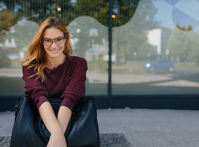 Portrait of smiling young woman sitting outdoors with bag - p300m2103043 by Gustafsson