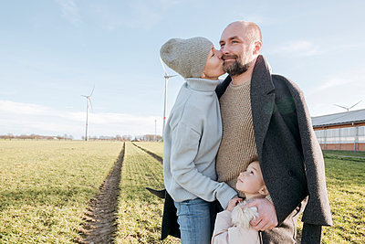 Happy parents with little daughter standing on a field in winter - p300m2181205 by Katharina und Ekaterina